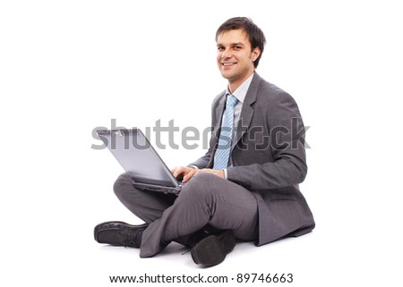 Young businessman sitting on the floor and typing on a laptop - stock photo