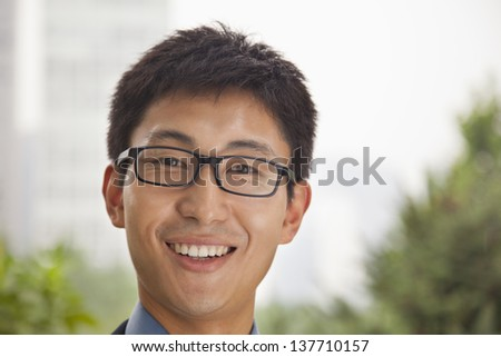 Young businessman smiling in the park, portrait - stock photo