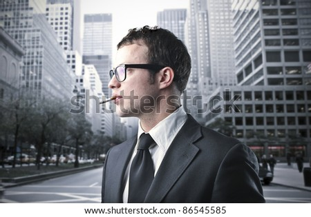 Young businessman smoking a cigarette on a city street - stock photo