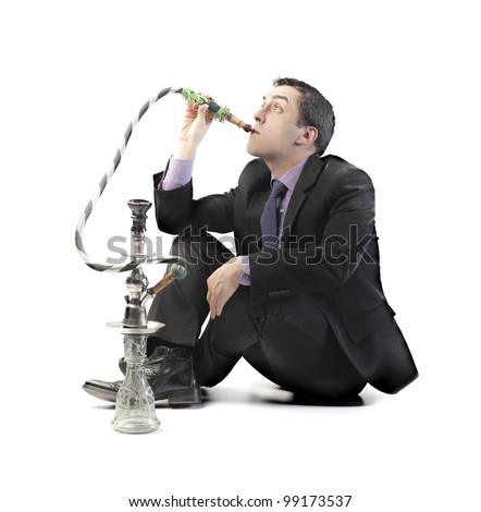 Young businessman smoking a hookah - stock photo