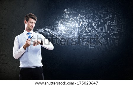 Young businessman smoking pipe with diagrams and graphs at background - stock photo