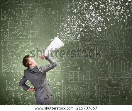 Young businessman speaking in trumpet with business sketches on wall - stock photo