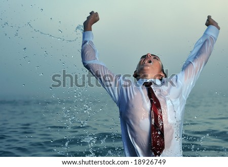 Young businessman splashing in water, close up - stock photo
