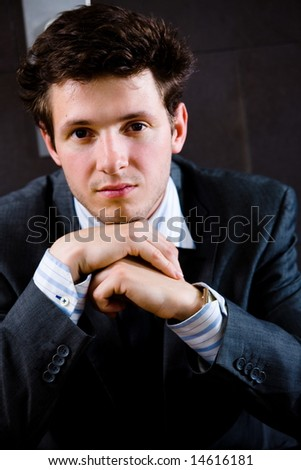 Young businessman squat on office corridor and thinking, looking at camera, daydreaming. - stock photo