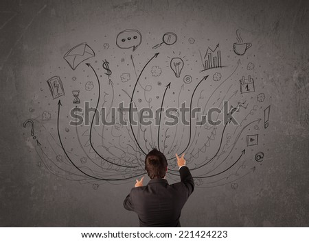 Young businessman standing and deciding in front of a chalkboard with sketched arrows and signs in different directions - stock photo