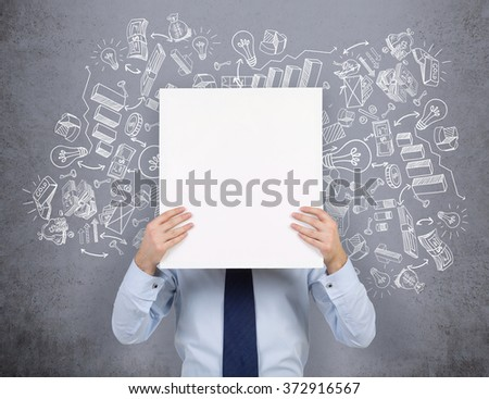 young businessman standing and holding a blank white poster so that he hides his head, numerous business symbols drawn over his head. Concrete background. Concept of developing a business. - stock photo