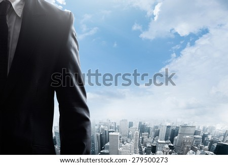 Young businessman standing  and looking at the city New York City Manhattan downtown view - stock photo