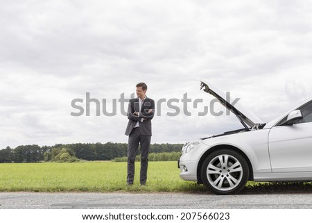 Young businessman standing arms crossed by broken down car at countryside - stock photo