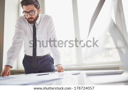 Young businessman standing by the window in office and working with papers - stock photo