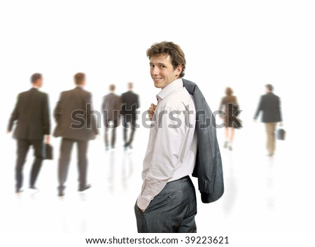 Young businessman standing his suit draped over his shoulder, looking back. Businesspeople moving in the background, isolated on white. - stock photo