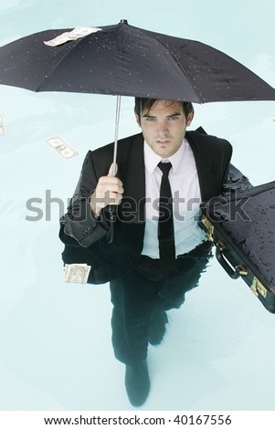 Young businessman standing in a pool with an umbrella. - stock photo