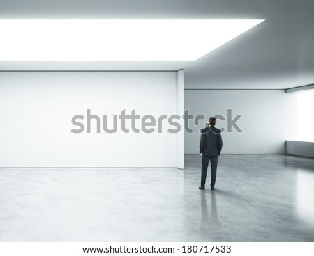 Young businessman standing in bright office  - stock photo