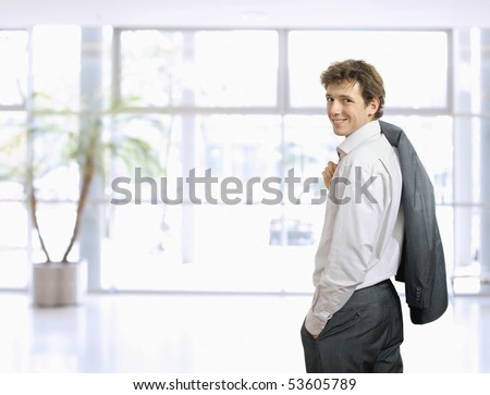 Young businessman standing in confident pose with hands in pocket and his suit draped over his shoulder. Looking back, smiling. - stock photo