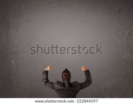 Young businessman standing in front of a wall with copy space - stock photo