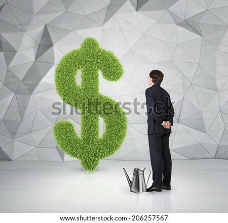 Young businessman standing in front of big dollar sign which is made of grass. A metaphor of prosperity.  - stock photo