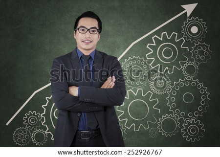 Young businessman standing in front of business gear to success  - stock photo