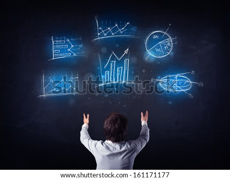 Young businessman standing in front of glowing charts and diagrams - stock photo