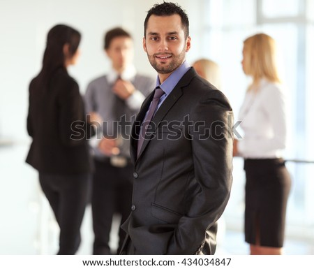 Young businessman standing in front of his associates - stock photo