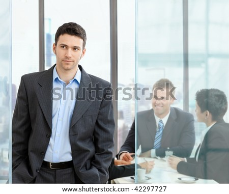 Young businessman standing in modern glass office, businesspeople having a meeting in the background. - stock photo