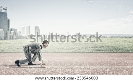 Young businessman standing in start pose ready to run - stock photo