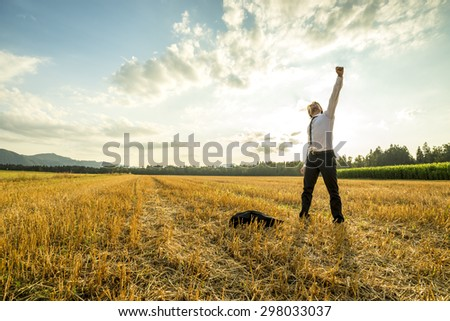 Young Businessman Standing in the Field and Raising his Arm for Success While Throwing his Coat on the Ground. - stock photo