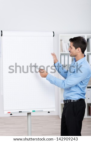 Young businessman standing near a flipchart and explaining the numbers. - stock photo