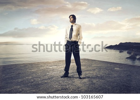 Young businessman standing on a beach - stock photo