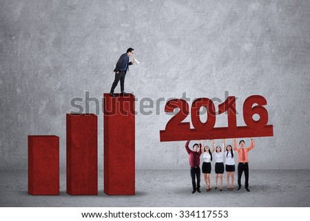 Young businessman standing on business chart and using a megaphone to give order on his partners to lift numbers 2016 - stock photo