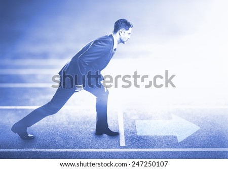 young businessman standing on running track for athletics and competition - stock photo