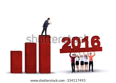Young businessman standing on the financial chart and giving motivation with a megaphone on his partners to lift numbers 2016 - stock photo