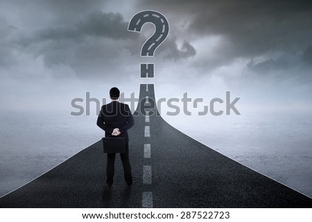 Young businessman standing on the highway while looking at a question symbol - stock photo