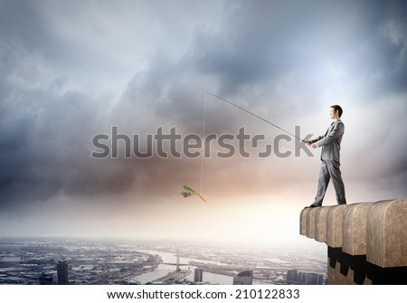 Young businessman standing on top of building and fishing - stock photo