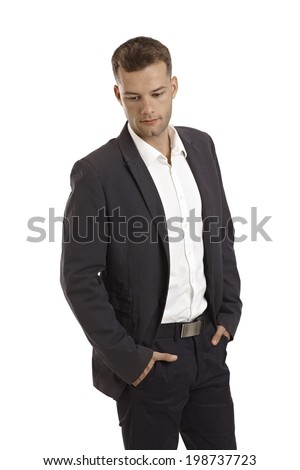 Young businessman standing with hands in pockets, looking down. - stock photo