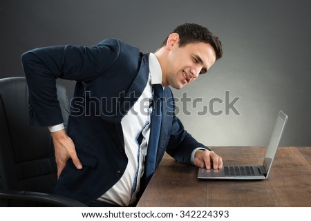 Young businessman suffering from back pain while working on laptop at desk against gray background - stock photo