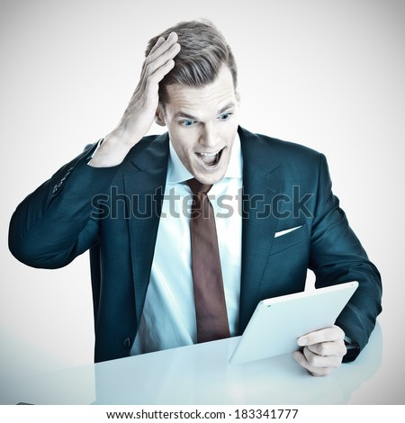 Young businessman suprised by what he sees on his tablet pc - stock photo