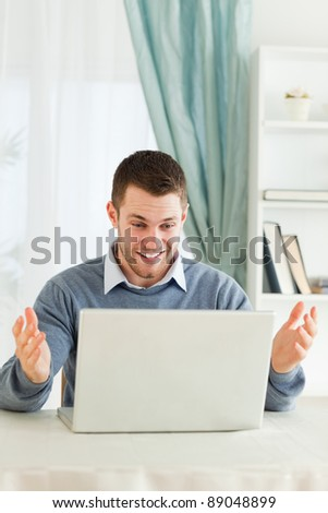 Young businessman surprised about his laptop in his home office - stock photo