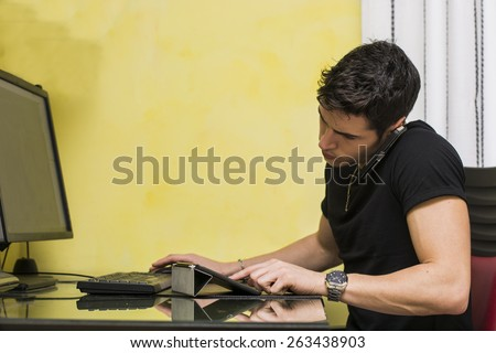 Young businessman taking a frustrating call on his mobile phone sitting as he works at his desktop computer in the office or at home - stock photo