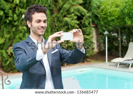 Young Businessman Taking Photos with Mobile, Italy - stock photo
