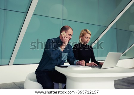 Young businessman talking on mobile phone with client while his secretary keyboarding on net-book, male and female economists using cell telephone and laptop computer while working together in office - stock photo
