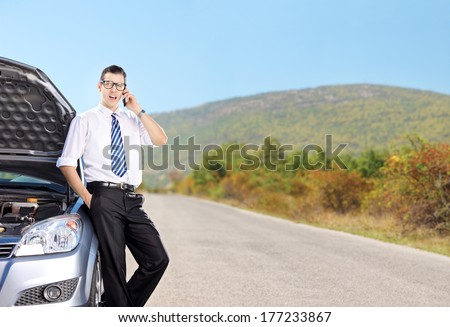 Young businessman talking on phone next to a car on an open road, shot with tilt and shift lens - stock photo