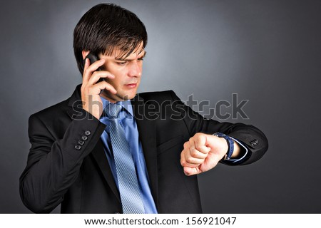 Young businessman talking on phone while looking at his watch isolated on gray background - stock photo