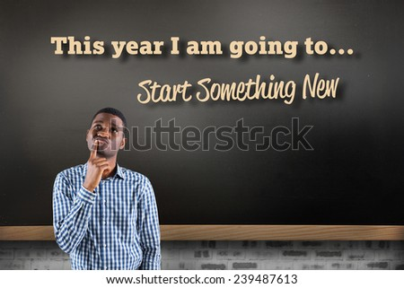 Young businessman thinking against blackboard on wall - stock photo