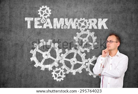 young businessman thinking and drawing teamwork concept on concrete wall - stock photo