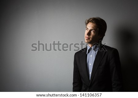 Young businessman thinking and having ideas on a gray background with copy-space on the left - stock photo
