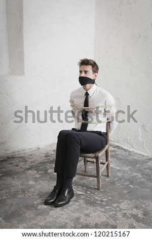 Young businessman tied to a chair in a basement - stock photo