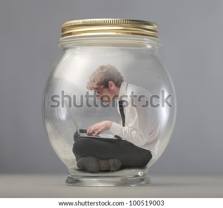 Young businessman trapped in a glass jar and using a laptop - stock photo