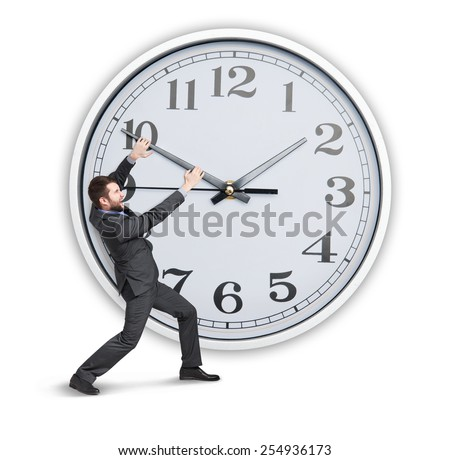 young businessman trying to stop a time. isolated on white background - stock photo