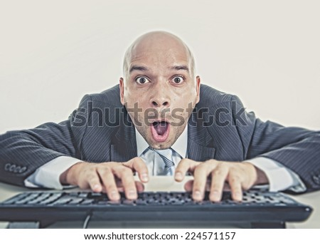 young businessman typing on computer keyboard with funny face expression on watching porn online and internet chat and social network addiction concept isolated on white background - stock photo