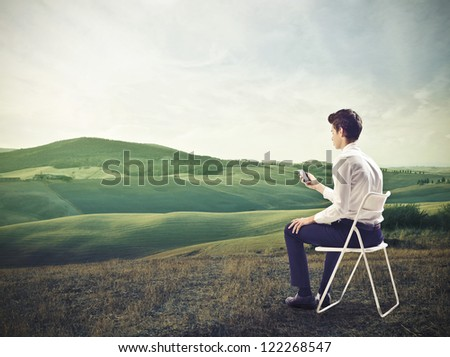 Young businessman using a mobile phone sitting on a chair in a beautiful landscape - stock photo