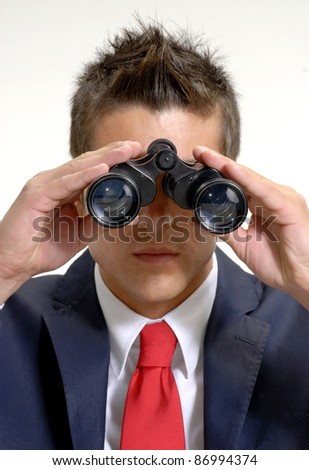 Young businessman using binoculars. - stock photo